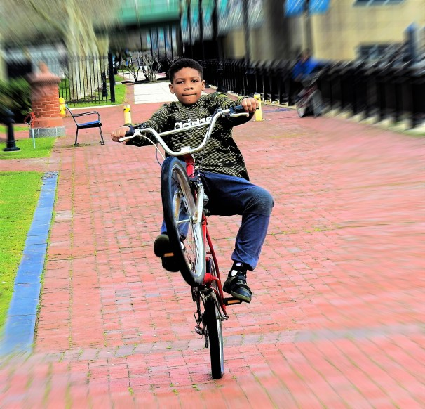 A boy doing a 'wheelie' on his bicycle.